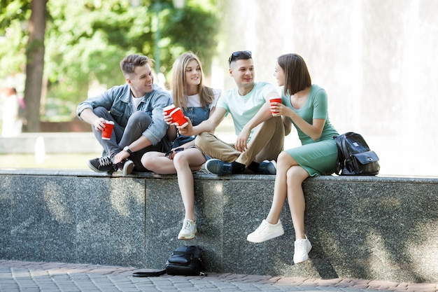 Jóvenes atractivos que se divierten juntos al aire libre. gente bebiendo café y sonriendo. grupo de amigos caminando juntos. Foto Premium