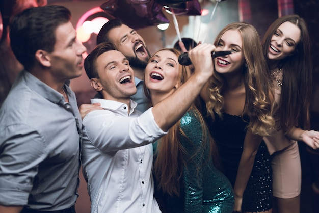Jóvenes en el club bailan y cantan. Foto Premium