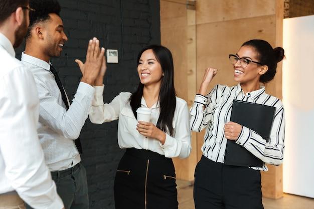 Los jóvenes colegas de negocios entusiasmados se dan la mano el uno al otro. Foto gratis