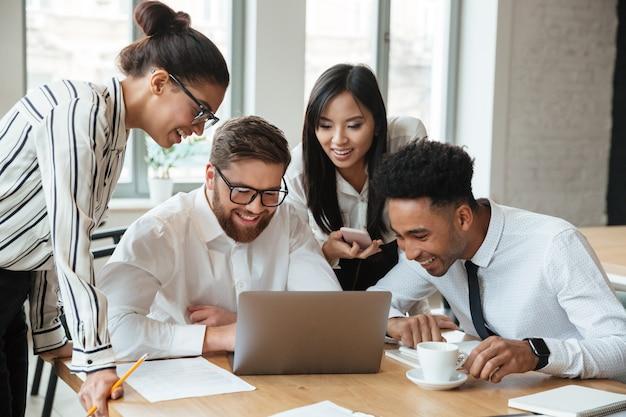 Jóvenes colegas de negocios feliz usando la computadora portátil. Foto gratis