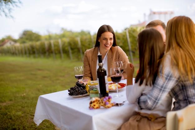 Los jóvenes disfrutan de una cena y cata de vinos en el viñedo. Foto Premium