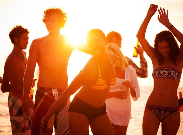 Jóvenes disfrutando de una fiesta en la playa de verano Foto gratis