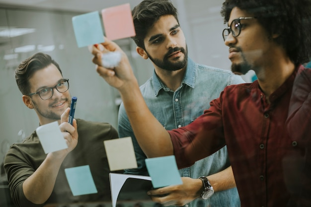 Jóvenes empresarios discutiendo frente a la pared de vidrio usando notas y calcomanías Foto Premium