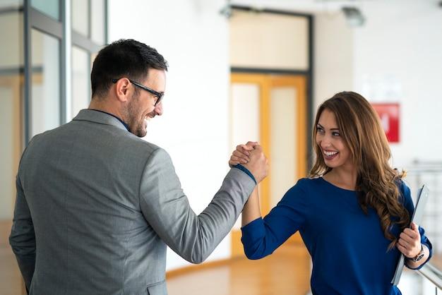 Jóvenes empresarios exitosos saludando en la oficina de la empresa Foto gratis