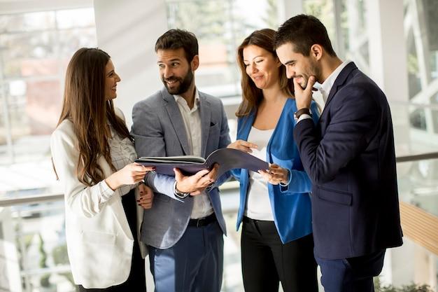 Jóvenes empresarios de pie y analizando documentos. | Foto Premium