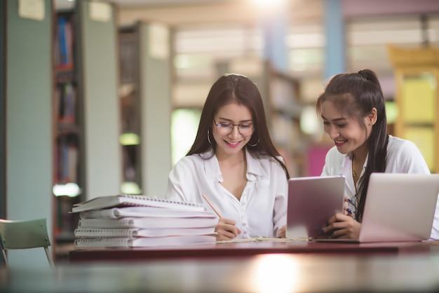 Jóvenes estudiantes aprendiendo, bibliotecas de estanterías. Foto gratis