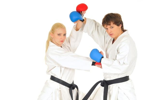 Jóvenes estudiantes de karateka en kimono blanco, cinturones negros en guantes de combate entrenan para practicar golpes con patadas y manos sobre un fondo blanco. Foto Premium