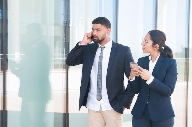 Jóvenes exitosos hombres de negocios usando teléfonos inteligentes Foto gratis