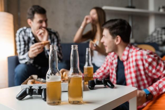 Jóvenes felices comiendo pizza, bebiendo cerveza, divirtiéndose, fiesta de amigos en casa, compañía hipster juntos, dos hombres una mujer, sonriendo, positivo, relajado, pasar el rato, reír, Foto gratis
