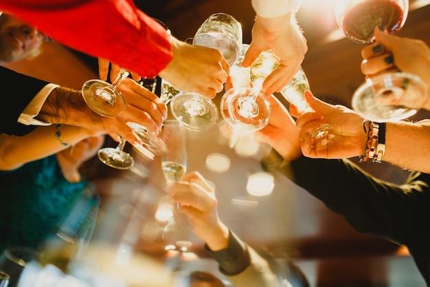 Jóvenes festejando haciendo tostadas con vasos y bebiendo alcohol. Foto Premium
