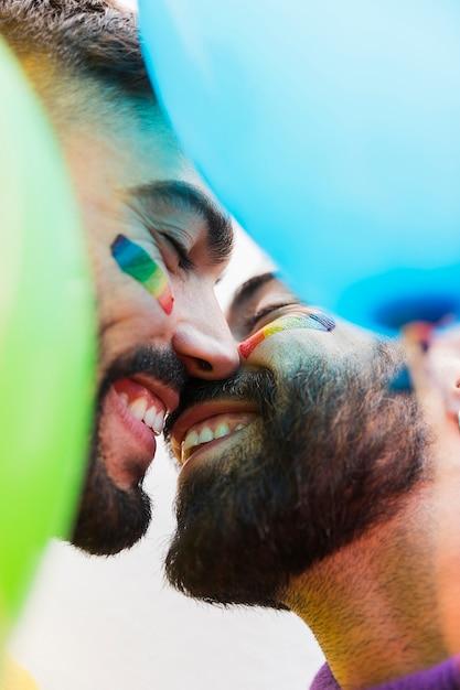 Jóvenes gays sonriendo mientras se besan Foto gratis