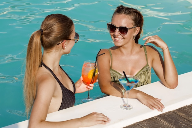 Jóvenes hermosas amigas charlando mientras toman unos tragos juntos en la piscina Foto Premium