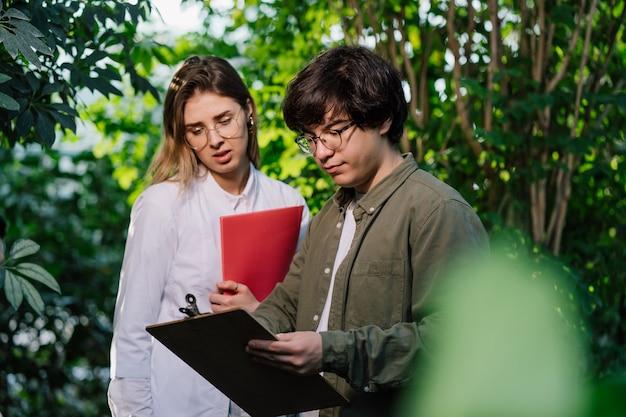 Jóvenes ingenieros agrícolas trabajando en invernadero Foto gratis