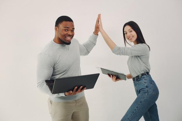 Jóvenes internacionales que trabajan juntos y usan la computadora portátil Foto gratis