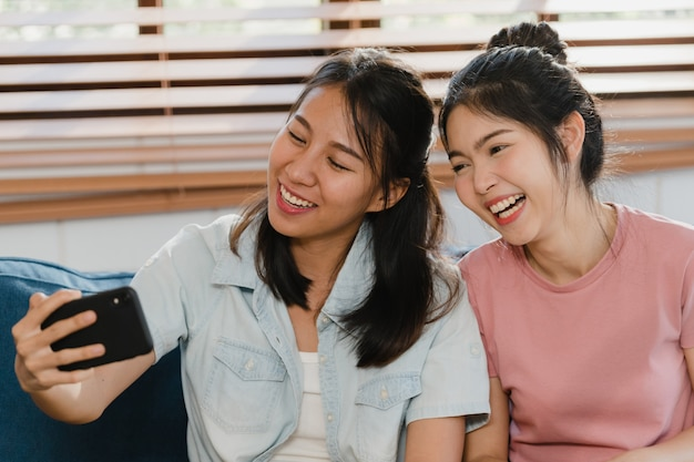Jóvenes lesbianas lgbtq mujeres pareja selfie en casa. Foto gratis