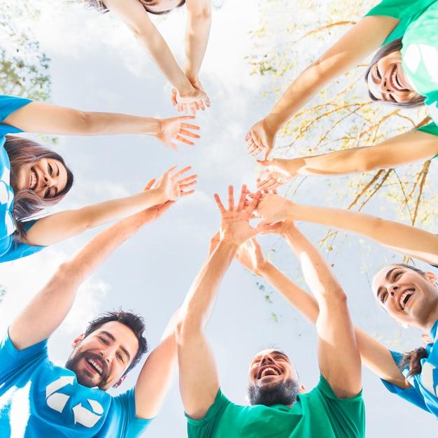 Jóvenes levantando las manos al cielo en círculo Foto gratis