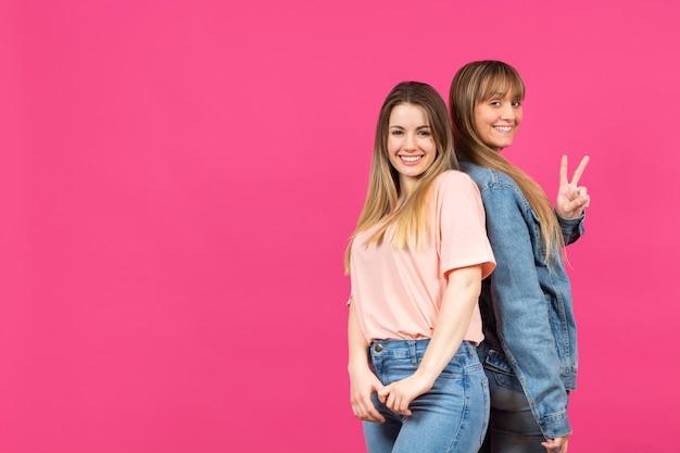 Jóvenes modelos posando con fondo rosa Foto gratis