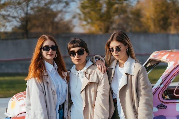 Jóvenes mujeres felices con bolsas de compras posando cerca de un viejo coche decorado Foto gratis