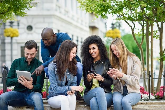 Jóvenes multiétnicos que usan computadoras con teléfonos inteligentes y tabletas Foto gratis