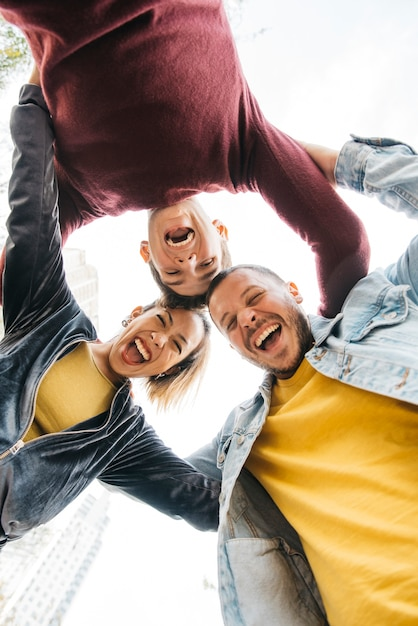 Jóvenes multirraciales amigos riendo y de pie en círculo Foto gratis