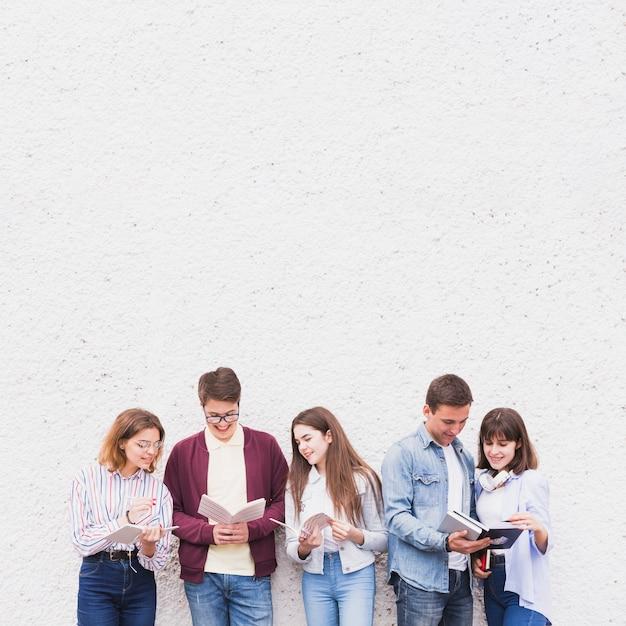 Jóvenes de pie y leyendo libros discutiendo contenido Foto gratis