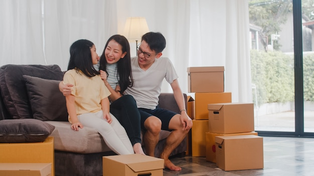 Los jóvenes propietarios de viviendas asiáticos felices compraron una casa nueva. los japoneses mamá, papá e hija se abrazan mirando hacia el futuro en un nuevo hogar después de mudarse en reubicación sentados juntos en un sofá con cajas. Foto gratis