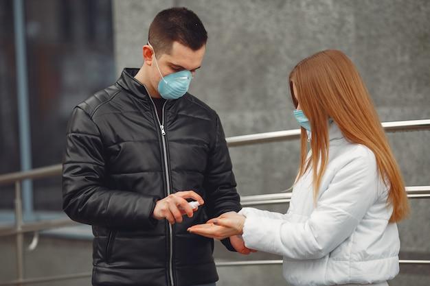 Los jóvenes que usan máscaras protectoras están rociando desinfectante para manos Foto gratis