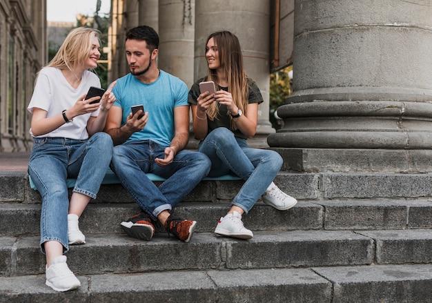 Jóvenes sentados en las escaleras y revisando sus teléfonos Foto gratis