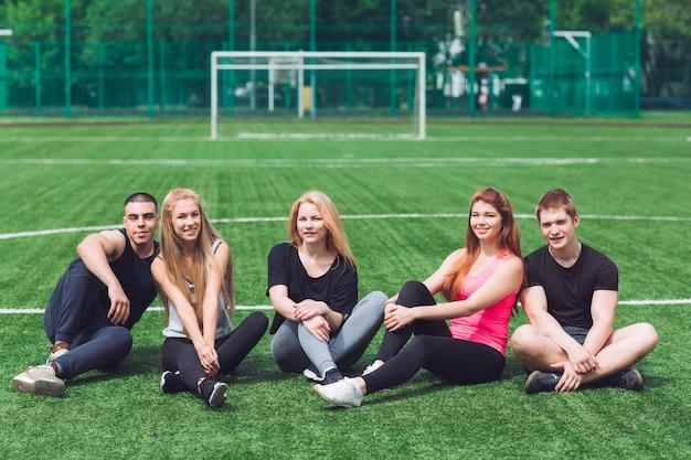 Los jóvenes se sientan en la hierba en el campo de fútbol. Foto Premium