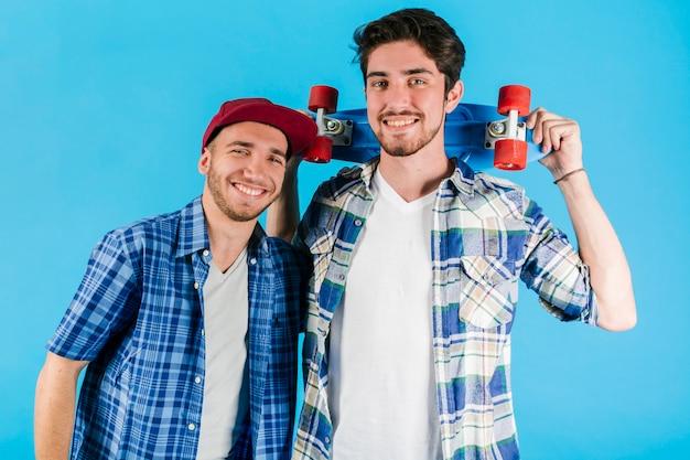Jóvenes sonrientes amigos con penny skate Foto gratis