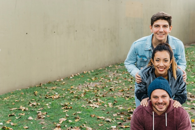 Jóvenes sonrientes multirraciales amigos de pie uno tras otro Foto gratis