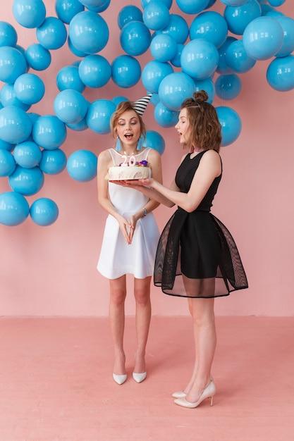Los jóvenes sorprendieron a la muchacha que sostenía una torta de cumpleaños y su amigo que se colocaban cerca. Foto gratis