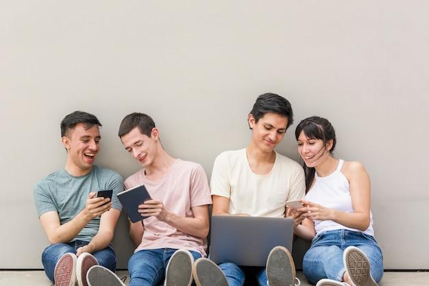 Jóvenes con teléfonos y laptop Foto gratis
