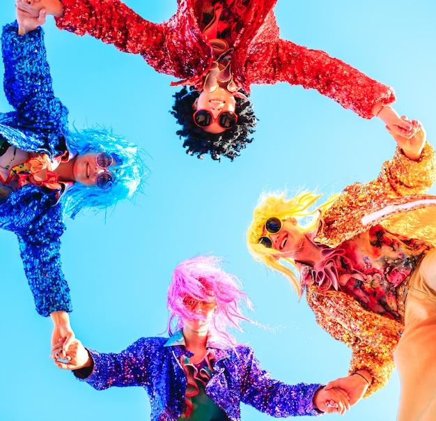 Jóvenes en zancos posando contra el cielo azul. Foto Premium