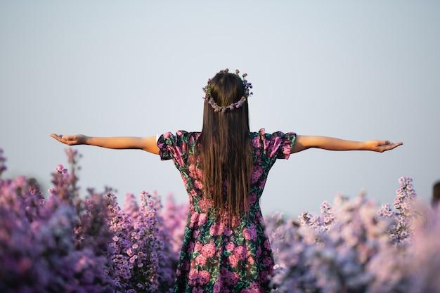 Joyfull mujer en vestido morado entre flor de margarita púrpura Foto gratis