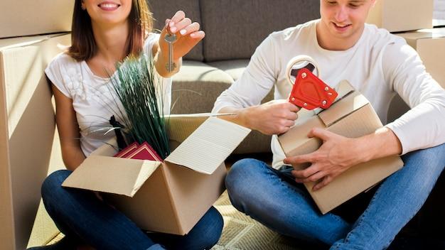 Joyfull pareja empacando cosas en cajas de cartón Foto gratis
