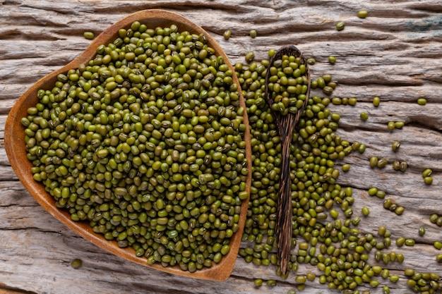 Judías verdes crudas en una taza colocada en un piso de madera. Foto gratis