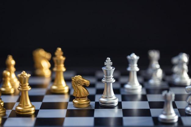 Juego de ajedrez, establece el tablero esperando jugar en piezas de oro y plata desenfocado Foto Premium