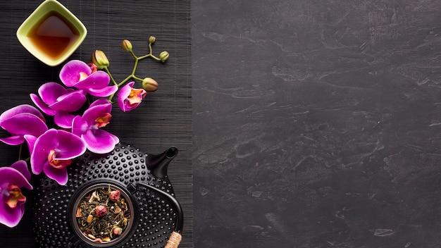 Juego de té asiático con flor de orquídea e ingrediente de té seco en mantelito negro Foto gratis