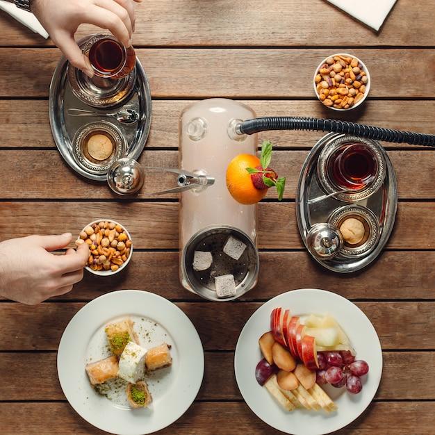 Juego de té con bocadillos dulces y frutas vista superior Foto gratis