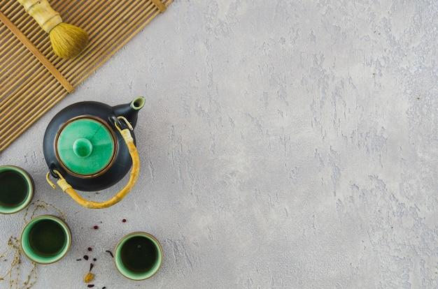 Juego de té tradicional con pincel en mantel sobre el fondo de hormigón gris Foto gratis