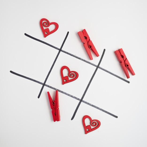 Juego de tic tac toe con corazones y pins. Foto gratis