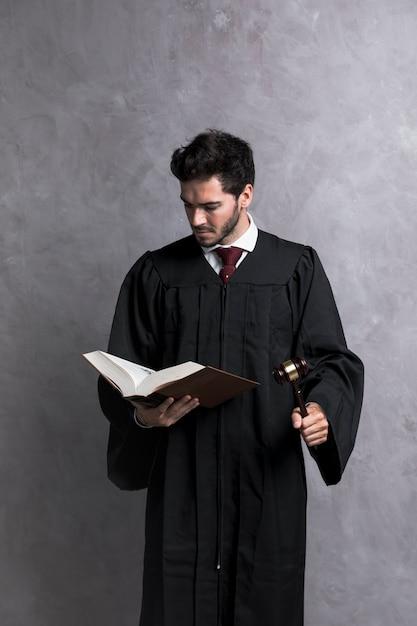 Juez de vista frontal con libro de lectura de martillo Foto gratis