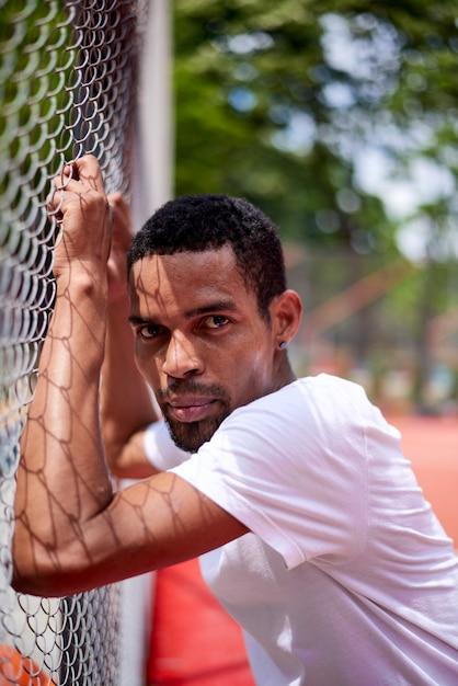 Jugador de baloncesto negro sosteniendo la valla de alambre con las manos Foto Premium