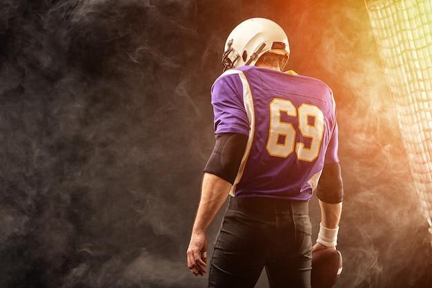 Jugador de fútbol americano con pelota en sus manos Foto Premium