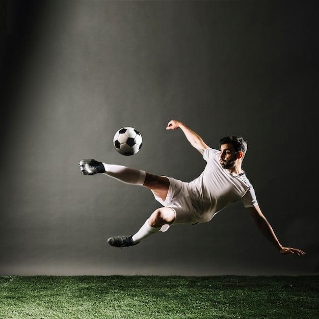 Jugador de fútbol barbudo cayendo y pateando la pelota Foto gratis