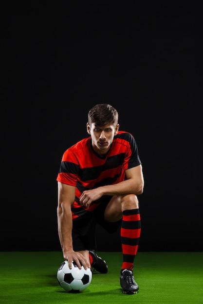Jugador de fútbol pateando la pelota, jugando al fútbol Foto gratis