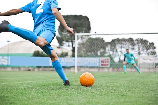Jugador de fútbol pateando la pelota Foto Premium