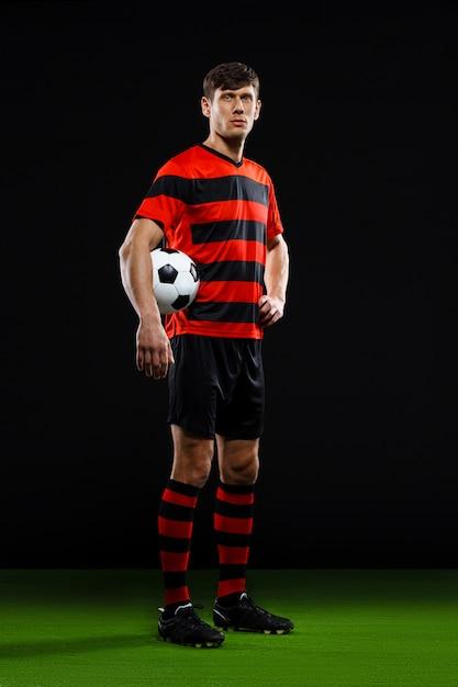 Jugador de fútbol seguro con balón, jugar al fútbol Foto gratis
