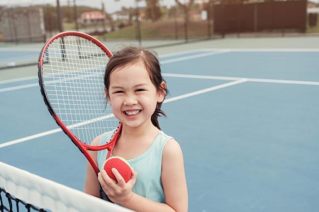 Jugador de tenis asiático joven de la muchacha en corte azul al aire libre Foto Premium